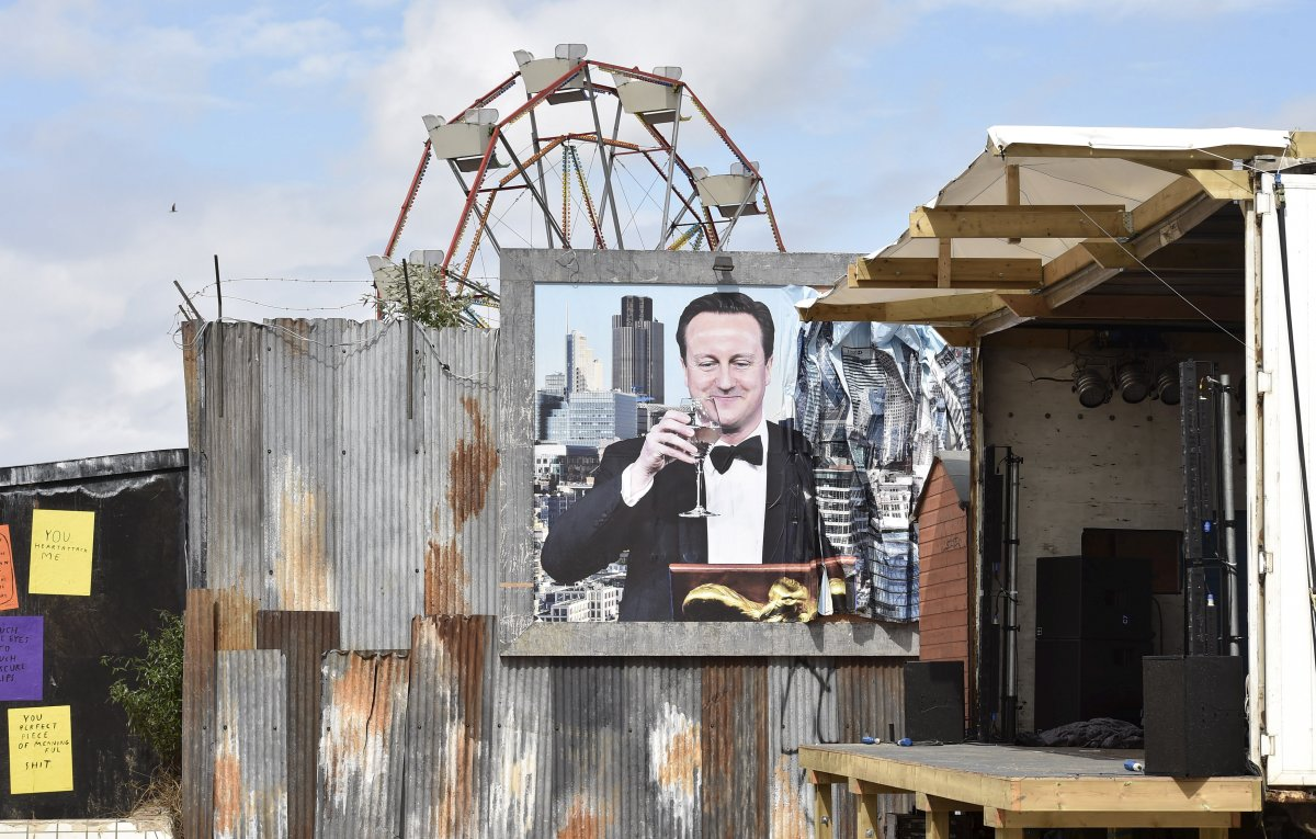 this-smiling-portrait-of-british-prime-minister-david-cameron-looks-down-from-a-damaged-billboard-next-to-an-outdoor-film-screening